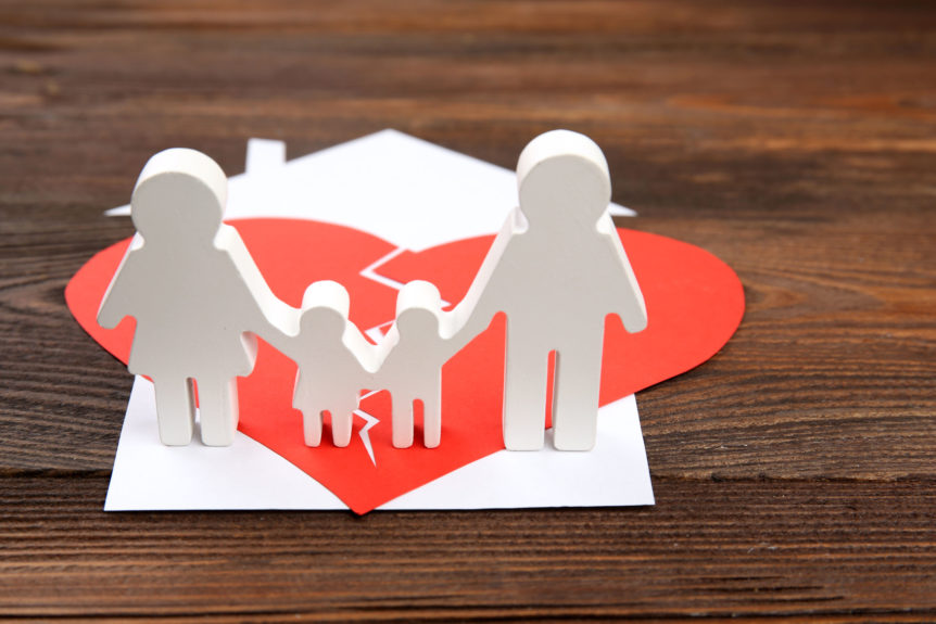 A paper cutout silhouette of a family split apart on a paper heart on desk.