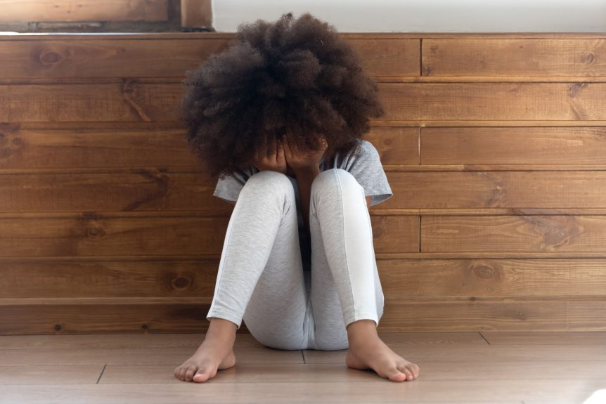 Sad stressed little african american girl crying, upset lonely bullied child feels abandoned abused, preschool black orphan kid in tears sit alone on floor, children abuse, domestic violence, unhappy childhood concept