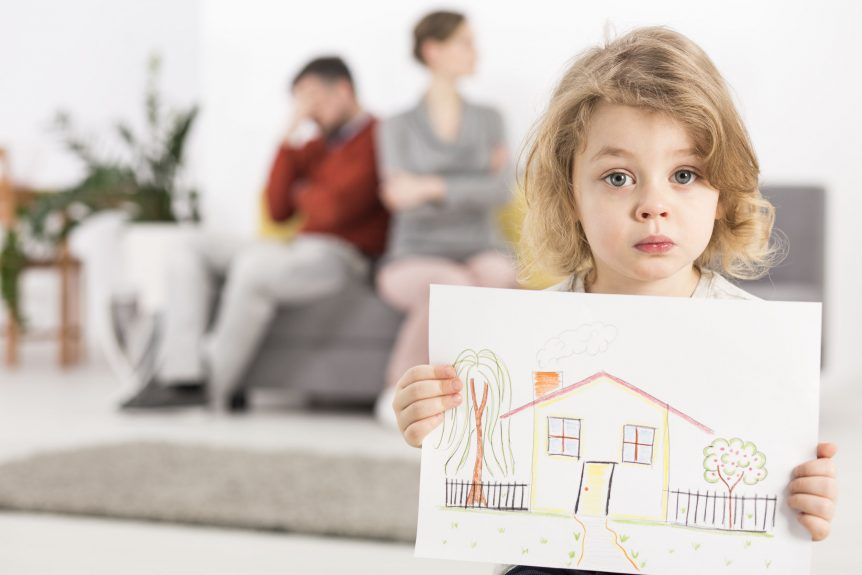 Upset little boy holding a drawing of a house, with his parents are upset about divorce while sitting on a couch in the blurry background