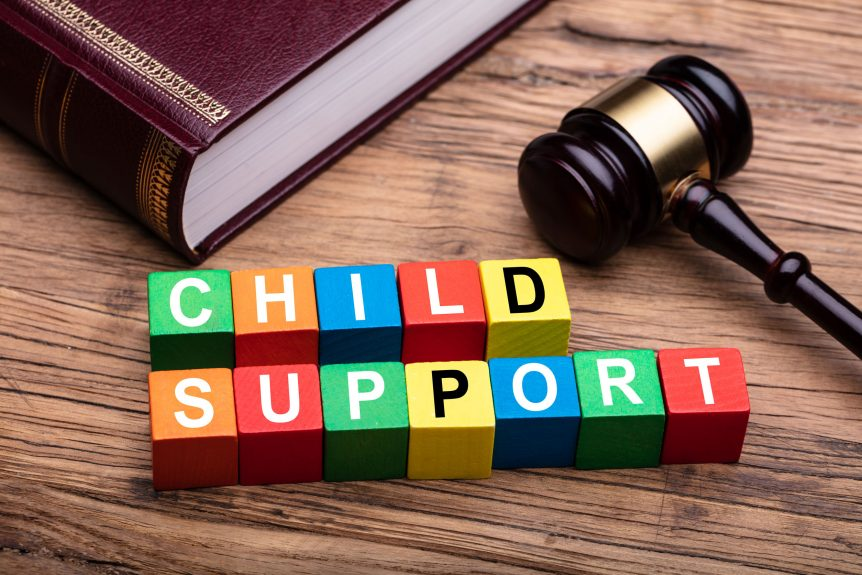 Child Support Colorful Block With Bible And Hammer Over Wooden Desk In Courtroom, ruling payments for child support