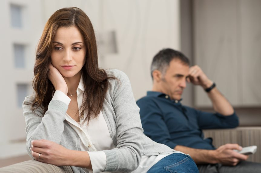 Sad Couple Sitting On Couch After Having Quarrel. Sad couple considering filing for divorce.