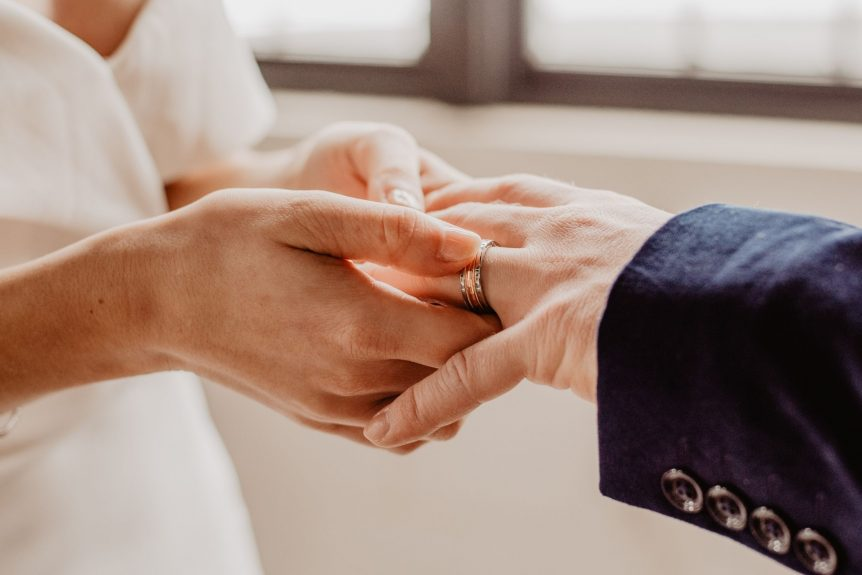 Couple getting remarried after having a divorce. Bride putting wedding ring on groom's hand.