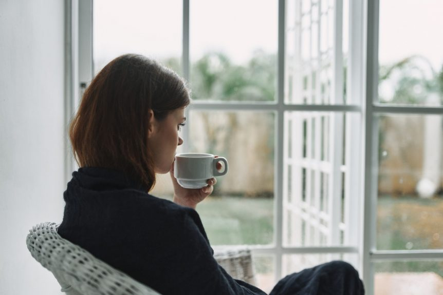 woman sitting in front of window while drinking coffee and contemplating how to overcome emotional abuse caused due to domestic violence