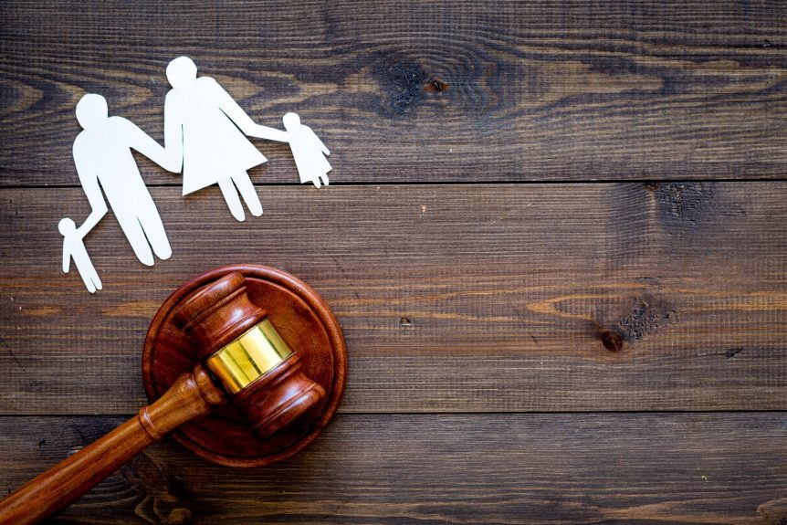 Paper family next to gavel while representing family law and child custody