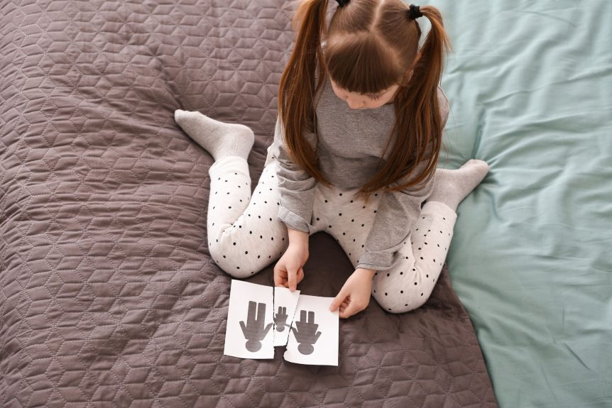 divorce with kids is very hard for young children, kid looking at broken family picture while sitting on bed