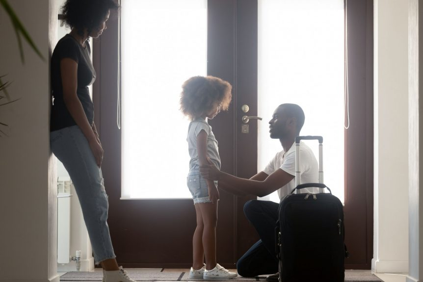 child custody agreement where mom keeps the child and child is saying goodbye to dad who already has a suitcase