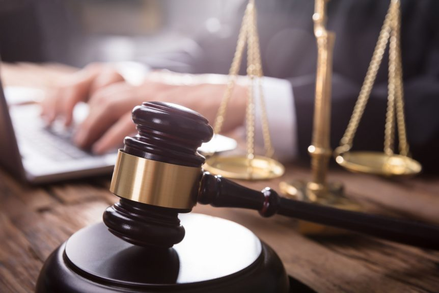 online divorce lawyer working on laptop behind Gavel And Justice Scale