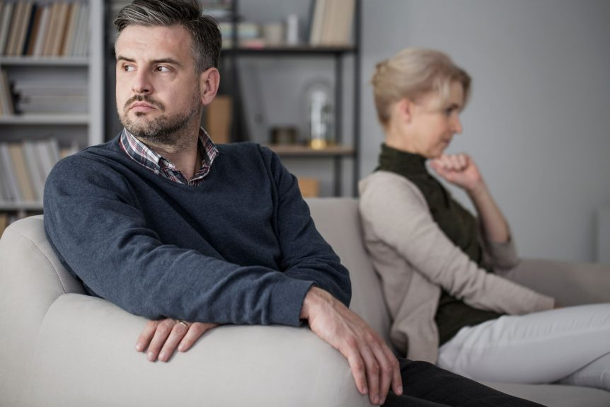 couple considering getting a divorce while sitting on couch and not speaking to each other