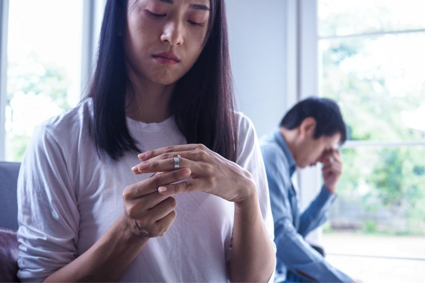 woman looking at wedding ring while considering getting a divorce and her husband sits behind her