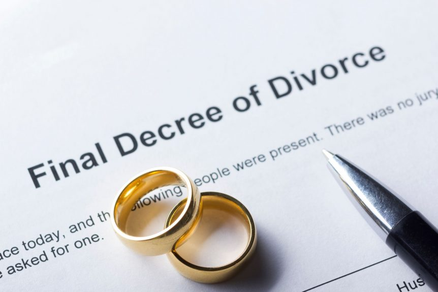 paperwork for getting divorced under wedding rings and pen